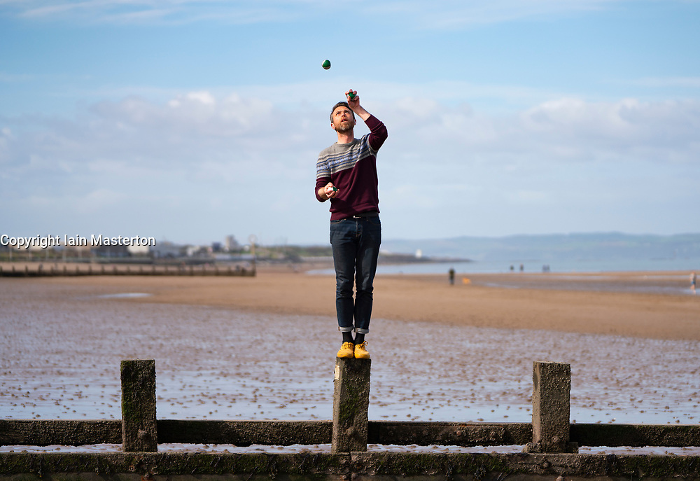 Portobello, Edinburgh. Scotland, UK. 12 April, 2020. Easter Sunday afternoon in sunny weather the public are outdoors exercising and walking on Portobello beach. The popular beach and promenade was very quiet and people were mostly exercising proper social distancing. Pictured; Man juggling on portobello Beach. Iain Masterton/Alamy Live News