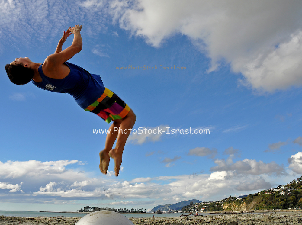Young man somersaulting on the beach. Photographed in Nelson New Zealand. Model Re1lease Availanle