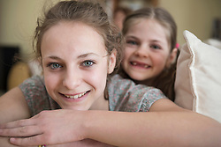 Portrait of sisters sitting on couch in living room, smiling