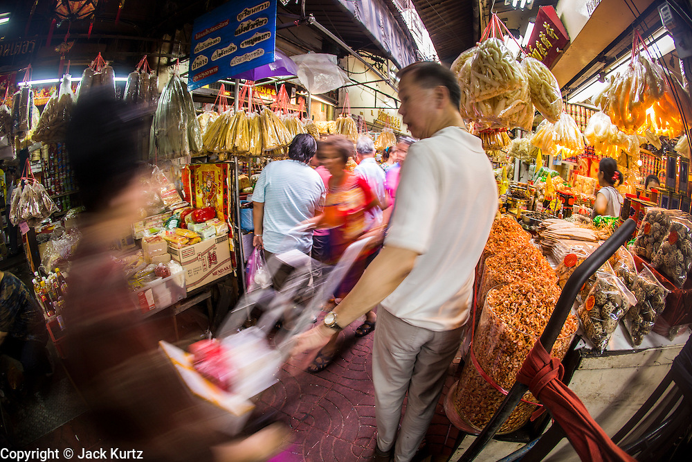 14 OCTOBER 2012 - BANGKOK, THAILAND:  An alley in Bangkok's Chinatown on the first day of the Vegetarian Festival. The Vegetarian Festival is celebrated throughout Thailand. It is the Thai version of the The Nine Emperor Gods Festival, a nine-day Taoist celebration beginning on the eve of 9th lunar month of the Chinese calendar. During a period of nine days, those who are participating in the festival dress all in white and abstain from eating meat, poultry, seafood, and dairy products. Vendors and proprietors of restaurants indicate that vegetarian food is for sale by putting a yellow flag out with Thai characters for meatless written on it in red.     PHOTO BY JACK KURTZ