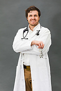 Male doctor wearing PPE, white coat and stethoscope