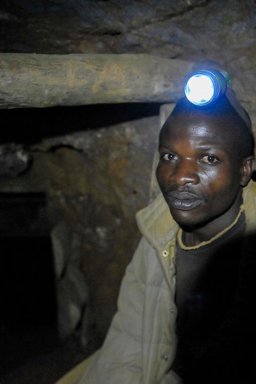 Gold mine in South Kivu, DRC Congo. A miner with a headlamp inside a mine shaft. Excavators like him chisel gold ore out of the earth and each day spent 6 to 8 hours down the shaft.  Murale, South Kivu, DRC. August 21, 2010.<br /> Mine d'or au Sud-Kivu, RDC Congo. Un creuseur avec une lampe frontale à l'intérieur d'un puits de mine. Des creuseurs comme lui extrayaient le minerai d'or de la terre et passent chaque jour 6 à 8 heures dans le puits. Murale, Sud Kivu, RDC. 21 août 2010.