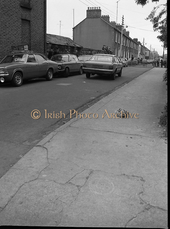 Scene Of Garda Shooting In North Strand.  (N78)..1981..26.05.1981..05.26.1981..26th May 1981..After a shootout in North Strand, Dublin, a Special Task Force Detective was shot and wounded. Word from The Richmond Hospital was that the detective was lucky to be alive as the bullet had narrowly missed a vital artery. He is said to be recovering after surgery..Image shows onlookers sitting on a wall at the scene of the Gardas' shooting.