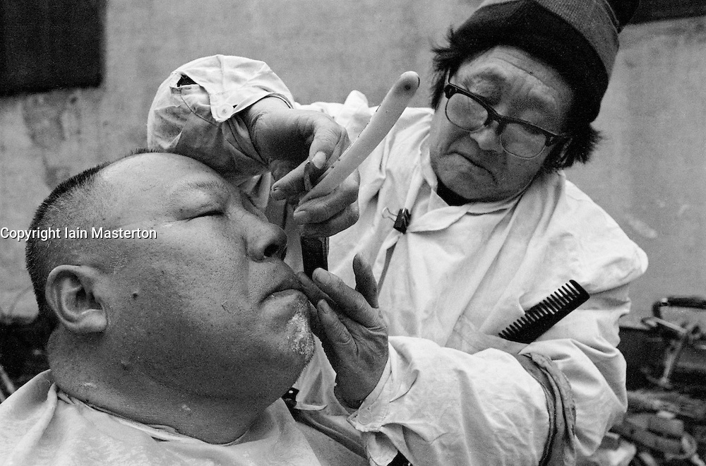 Man having a shave from barber in a Beijing hutong in Beijing China