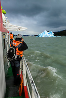A passenger takes a photo on the boat trip back from Glacier Grey in Torres del Paine National Park, Chile.