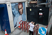 A man uses his phone to photograph the wider view of Piccadilly Circus, beneath a billboard featuring a male model, outside a brnch of GAP, on 9th July 2021, in London, England.