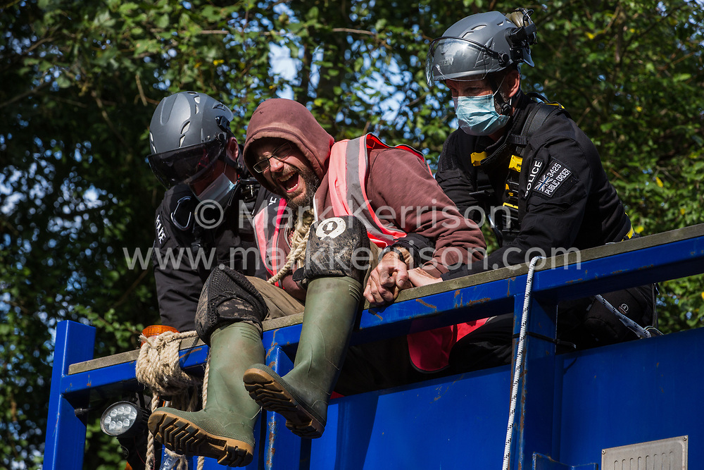 Denham, UK. 28th September, 2020. A Thames Valley Police officer uses force to remove the hand of an anti-HS2 activist glued to a HGV with a rope around his neck in order to block its passage to works for the HS2 high-speed rail link. Environmental activists continue to try to prevent or delay works on the controversial £106bn project for which the construction phase was announced on 4th September from a series of protection camps based along the route of the line between London and Birmingham.