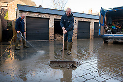 © Licensed to London News Pictures. 29/12/2015. York, UK. Two men sweep away mud left by flood water on Huntington Road in central York. Further rainfall is expected over coming days as Storm Frank approaches the east coast of the country. Photo credit: Ben Cawthra/LNP
