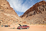 A broken down car with a popped hood below sandstone cliffs in Wadi Rum, Jordan.