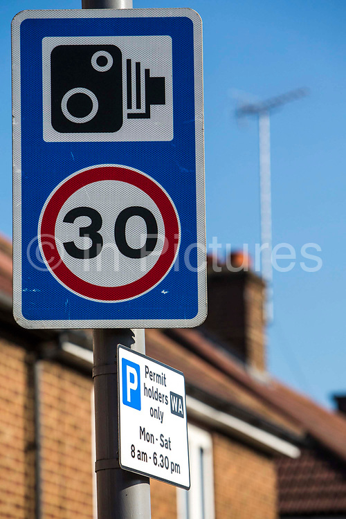 A speed camera warning sign on Forest Road next to a doulbe speed camera. Walthamstow, London.