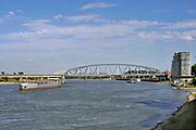 Nederland, Nijmegen, 25-6-2020 Binnenvaartschip, een tankschip, vaart over de Waal bij Nijmegen . Ter hoogte van de Honig en het nieuwbouwwijk Nijmegen- west, waalfront, passeren ze de nieuwe waalbrug de Oversteek . De Waal is het Nederlandse deel van de Rijn en de belangrijkste vaarroute van en naar Rotterdam en Duitsland . Aftakkingen zijn de minder bevaren Neder Rijn en IJssel. Foto: ANP/ Hollandse Hoogte/ Flip Franssen