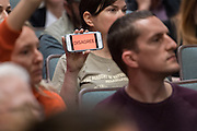 "A member of the audience holds up her phone with the word ""Disagree"" during a heated discussion with U.S. Sen. Tim Scott and U.S. Rep. Mark Sanford at a town hall meeting February 18, 2017 in Mount Pleasant, South Carolina. Hundreds of concerned residents turned up for the meeting to address their opposition to President Donald Trump during a vocal meeting held by U.S. Rep. Mark Sanford and Senator Tim Scott."
