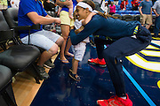 Skylar Diggens of the Dallas Wings hugs Charlie Muehlhausen, 2, as she leaves the court against the Connecticut Sun during a WNBA preseason game in Arlington, Texas on May 8, 2016.  (Cooper Neill for The New York Times)