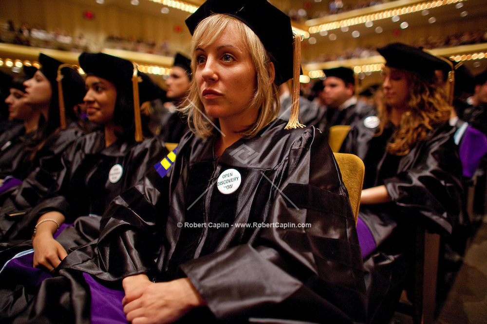 """Cardozo School of Law graduates wear """"Open Discovery Now"""" pins during their commencement at Avery Fisher Hall in Lincoln Center...Photo by Robert Caplin ."""