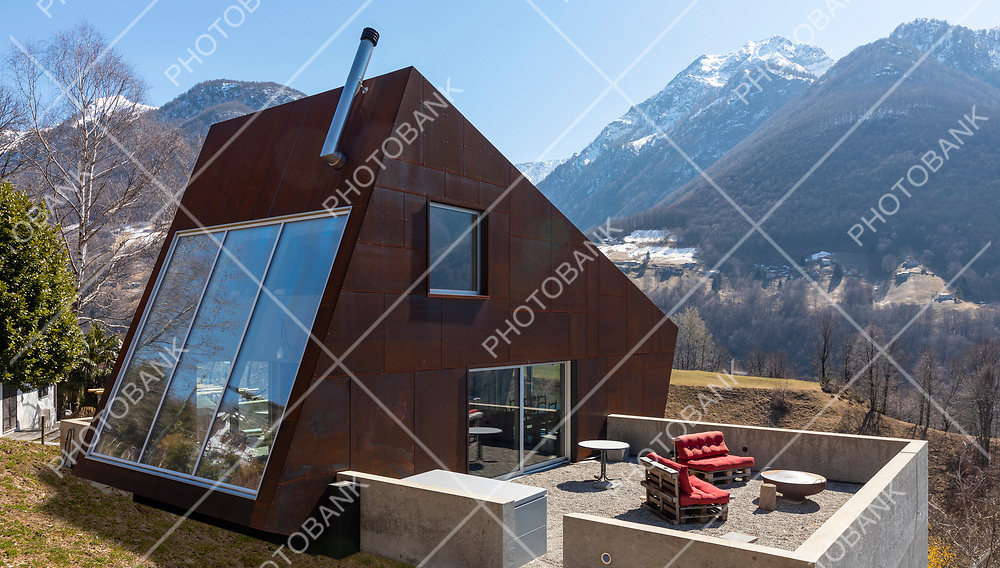 Back exterior of modern isolated villa with garden, surrounded by nature. Beautiful landscape of Swiss Alps. Nobody inside