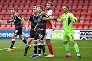 Jake Hessenthaler and Glenn Morris (1) of Crawley Town with Andy Williams (14) of Cheltenham Town during the EFL Sky Bet League 2 match between Cheltenham Town and Crawley Town at Jonny Rocks Stadium, Cheltenham, England on 10 October 2020.