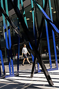 A City worker walks past the sculpture entitled Cosmos, an artwork by Eva Rothschild in the City of London, the capitals financial district, on 24th September 2021, in London, England. Cosmos 2019 is composed of three 3.5m high slatted structures which lean and support each other and is part of the summers Art In The City project.