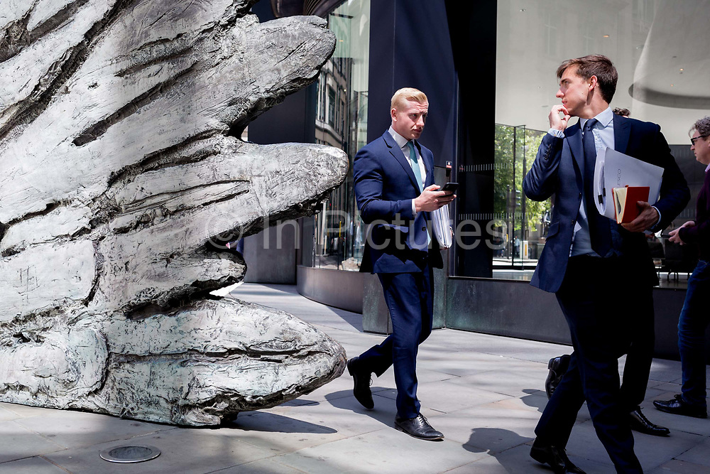City businessmen walk past the sculpture entitled City Wing on Threadneedle Street in the City of London, the capitals financial district, on 17th June 2019, in London, England. This ten-metre-tall bronze sculpture is by President of the Royal Academy of Arts, Christopher Le Brun, commissioned by Hammerson in 2009. 'The City Wing' and has been cast by Morris Singer Art Founders, reputedly the oldest fine art foundry in the world.