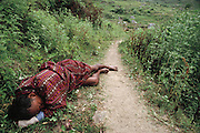 "A drunken Bhutanese man ""sleeping it off"" on the path at Shingkhey Village, Bhutan. From Peter Menzel's Material World Project."