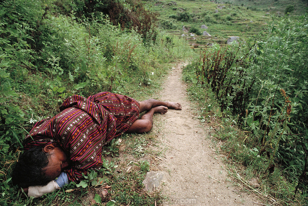 """A drunken Bhutanese man """"sleeping it off"""" on the path at Shingkhey Village, Bhutan. From Peter Menzel's Material World Project."""