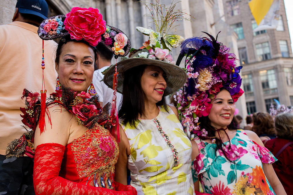 New York, NY - April 16, 2017. Three women in elaborate hats pose for photos of the steps of St. Patrick's Cathedral at New York's annual Easter Bonnet Parade and Festival on Fifth Avenue.
