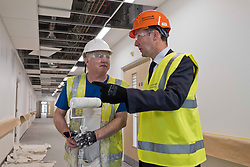 Pictured: Mr Matheson chatted to Painter Stephen McMullan as he put the finishing touches to the walls. <br /> <br /> Infrastructure Secretary Michael Matheson visited East Lothian Community Hospital's construction site today to give an update on the Scottish Government's infrastructure programme, on the same day as an annual progress report is published<br /> <br /> Ger Harley   EEm 17 April 2019