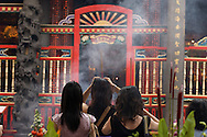 Three women pray using incense at Taipei Taiwan's Longshan Temple.