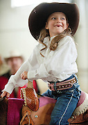 PRICE CHAMBERS / NEWS&GUIDE<br /> Future rodeo princess candidate Dally Wilson, 5, smiles with most of her teeth as she awaits her turn in the Heritage Arena on Saturday morning during the Teton County Fair and Rodeo Royalty Pageant. For a story and more photos of the annual contest, see Valley.