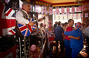 East end Londoners dance in a wave of nostalgia as they gather in their local east end pub in east London, England. Union Jack flags are everywhere - and even on a singer's acoustic guitar - as they remember the 50th anniversary of VE (Victory in Europe) Day on 6th May 1995. In the week near the anniversary date of May 8, 1945, when the World War II Allies formally accepted the unconditional surrender of the armed forces of Germany and peace was announced to tumultuous crowds across European cities, the British still go out of their way to honour those sacrificed and the realisation that peace was once again achieved. Street parties now – as they did in 1945 – played a large part in the country's patriotic well-being.