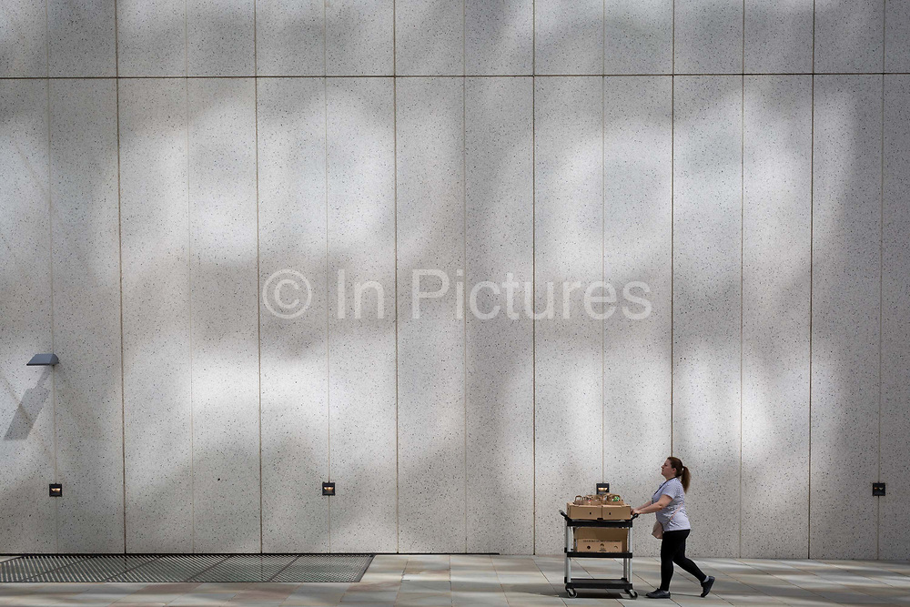 Beneath reflected light on a wall near the Barbican, a lady delivers catering supplies in the City of London, the capitals financial district - aka the Square Mile, on 8th August, in London, England.