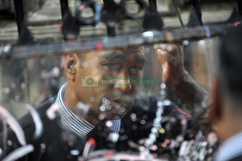October 19, 2016 - Kathmandu, NP, Nepal - A reflection seen on mirror as devotee puts tika or blessning on his forehead during a month Adinath Mela festival in Chobhar, Kirtipur, Kathmandu, Nepal on Wednesday, October 19, 2016. In the month of October or November from Kojagrat purnima to Kartik purnima for a month, people visit Adinath temple in the morning and perform special rituals puja and ritual function during Adinath Mela. (Credit Image: © Narayan Maharjan/NurPhoto via ZUMA Press)
