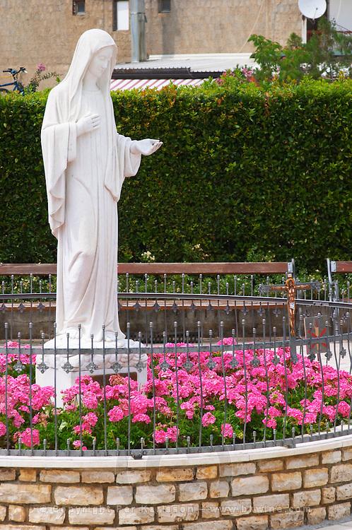 A statue of the Madonna in a flower bed in front of the church. Medugorje pilgrimage village, near Mostar. Medjugorje. Federation Bosne i Hercegovine. Bosnia Herzegovina, Europe.