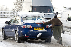 © under license to London News Pictures.  18/12/2010. A man helps to push a car stuck in snow in Datchet, Berkshire today (18/12/2010).  Severe weather is expected to hit the whole of the UK this weekend. Photo credit should read Sam Long/ London News Pictures