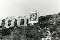 """1973 The Hollywood sign in disrepair. A """"save the sign"""" banner covers the letter D"""