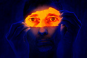 Blacklight portrait of a man holding a torn glowing print of his eyes in front of his face.