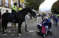 30 September 2017 - Premier League Football - Chelsea v Manchester City - A Chelsea fan on a mobility scooter chats with mounted police - Photo: Charlotte Wilson / Offside