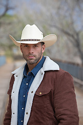 Portrait of a sexy rugged cowboy outdoors