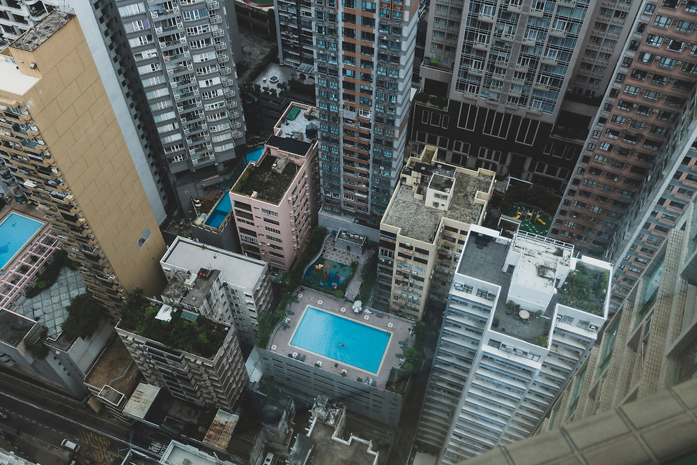 View from a high rise apartment building looking down on a man swimming in a rooftop pool in the Mid-Levels district of Hong Kong Island. (August 31, 2019)