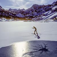 Cross country skier skiis by Lake Sabrina in Eastern Sierra Nevada, CA.
