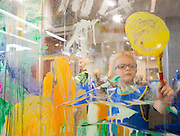 Jaxon Ledbetter, 5, of Lowell, Ark., paints in the Art Studio at the Scott Family Amazeum on Friday, February 19, 2016, in Bentonville, Arkansas. The studio is a glass wall where children can paint and then use a squeegee to wipe away their work. Beth Hall for the New York Times