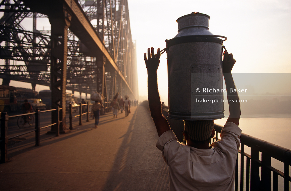 It is dawn in Calcutta, West Bengal, India and on the West bank of the Hooghly River the sun is rising from across the Howrah Bridge. The working day is beginning for this pedestrian seen carrying a large, heavy tank full of liquids, possibly on his way to market or a shop in Central Calcutta. Steady, he balances it weight though he can barely stretch up to grip the carrying handles. The bridge's engineering stretches across the water as the humanity cross to their businesses and markets. The British-built bridge is one of three on the Hooghly River and is a famous symbol of Kolkata and West Bengal. Bearing the daily weight of approximately 150,000 vehicles and 4,000,000 pedestrians. It is one of the longest bridges of its type in the world. The Hooghly River is an approximately 260 km long distributary of the Ganges River.