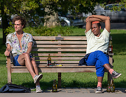 © Licensed to London News Pictures. 23/04/2020. London, UK. Two members of the public enjoy the warm weather at Primrose Hill as Londoners go out in the sunshine during lockdown as temperatures reach 24c. While an increase in traffic and people on the streets as members of the public face lockdown continuing till next month. Meanwhile, Ministers are still grappling with how to release people from the coronavirus pandemic lockdown. Photo credit: Alex Lentati/LNP