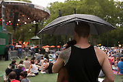A man and a woman watch the concert from under an umbrella during a brief period of rain.