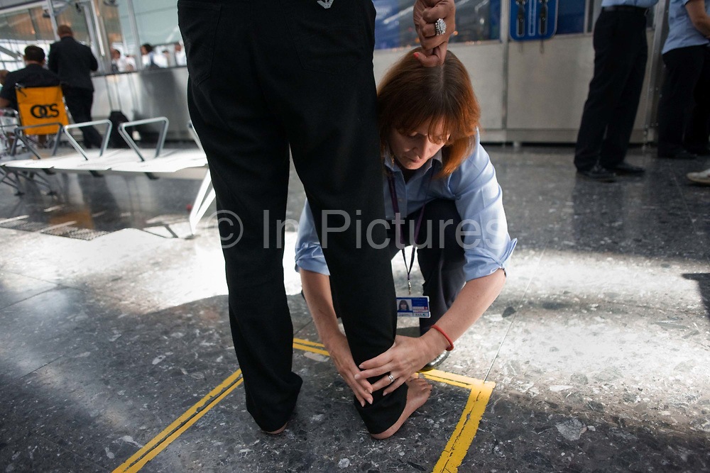 """Security employed by contractor OCS searches a passenger at Heathrow Airport's Terminal 5. Teams of 5-8 perform a rotational order of tasks, changing every 20 minutes: A loader (asking travellers to take off clothing, shoes etc); archway detectors; X-ray operator; liquid tester and bag searcher. The X-ray operator can earn a £50 bonus for a suspect item randomly inserted by undercover officials and known as an Airlock Find. Also, a Tip is a random image flashed on the screen that shows a suspect item they have to spot. A typical day of searched passengers is 25,000 passengers in T5. From writer Alain de Botton's book project """"A Week at the Airport: A Heathrow Diary"""" (2009)."""