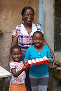 Linna Kinabo with two of her grandchildren who are holding a tray of eggs.<br /> <br /> Linna set up and now runs a poultry business selling both eggs and meat.<br /> <br /> She attended MKUBWA enterprise training run by the Tanzania Gatsby Trust in partnership with The Cherie Blair Foundation for Women.