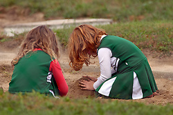 01 October 2016:  a pair of young girls dressed in IWU cheerleaders uniforms play just outside the stadium in the sand box at the end of the long jump during an NCAA division 3 football game between the Wheaton Thunder and the Illinois Wesleyan Titans in Tucci Stadium on Wilder Field, Bloomington IL (Photo by Alan Look)