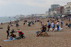 © Licensed to London News Pictures. 14/06/2014. Brighton, UK. People on Brighton beach. Cloudy and the occasional shower hasn't stopped people from visiting Brighton and spending the day at the beach. Photo credit : Hugo Michiels/LNP