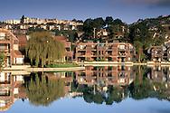 Affluent condominiums, townhomes and hills reflected in suburban man-made lake, Tiburon, Marin, California