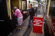 A volunteer helps an elderly lady from the platform up into a train carriage at the Paignton steam museum.