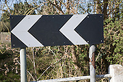 Black and white chevron road sign warning at a corner, UK